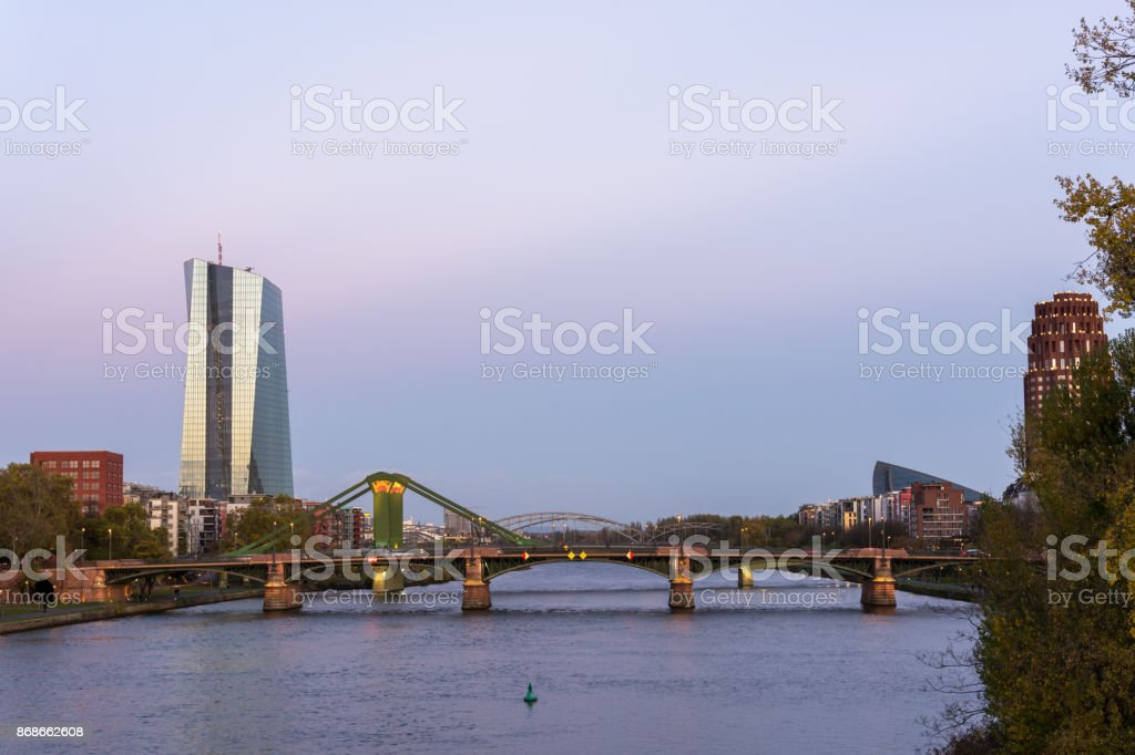 The EZB building in Frankfurt in the blue hour with a bridge in front and beautiful colors in the sky stock photo