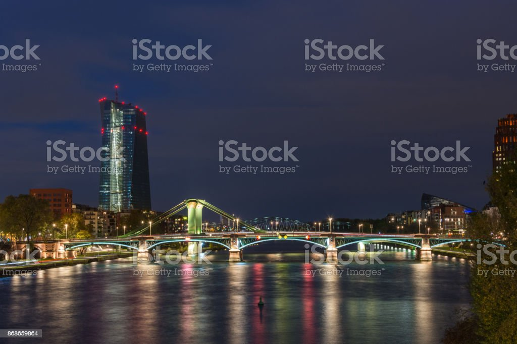 The EZB building in Frankfurt with red lights during blue hour with a lit bridge in front stock photo