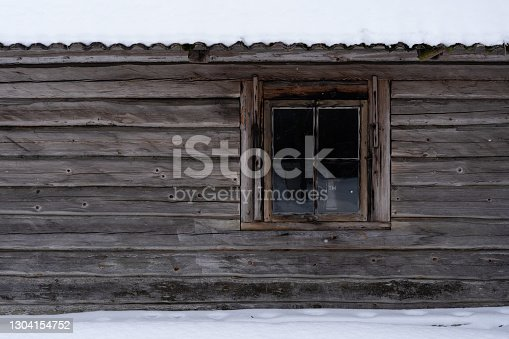 The facade of an old wooden log building with a small window divided into 4 parts and inside you can see a cup placed on a table, the roof is covered with snow and there is also white snow around the building itself.