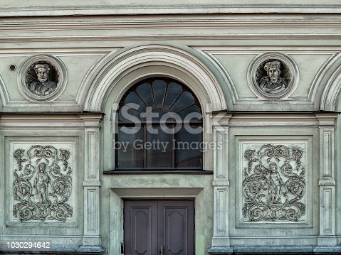 istock The facade of the building with two bas-reliefs, a sculptural panel, a door and a round stained-glass window in St. Petersburg 1030294642