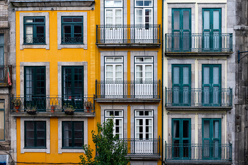 The facade of traditional building with beautiful windows at the Baixa neighborhood in the city of Porto