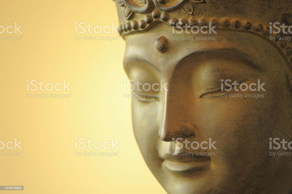 The face of a statue of Buddha on a yellow background stock photo