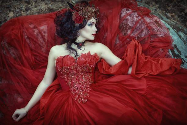 die fee in einem roten kleid liegt auf einem felsen - elfenkostüm damen stock-fotos und bilder