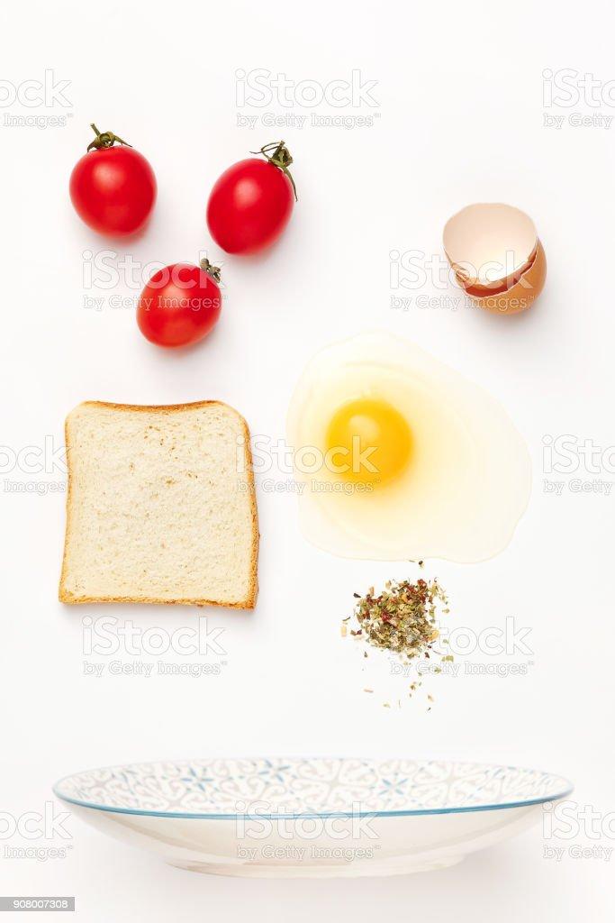 The falling ingredients of fried egg. Healthy breakfast ingredients stock photo