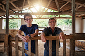 Cropped shot of a mature farmer and his young son standing in a barn on the family farm