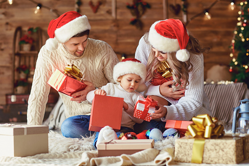 The family gives gifts to the child in the room with the Christmas tree.