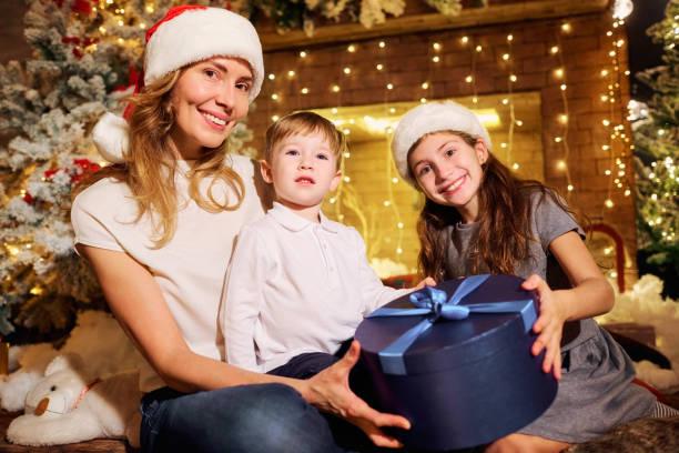 die familie gibt präsentiert in einem raum am weihnachtstag. - 4 monat schwanger stock-fotos und bilder