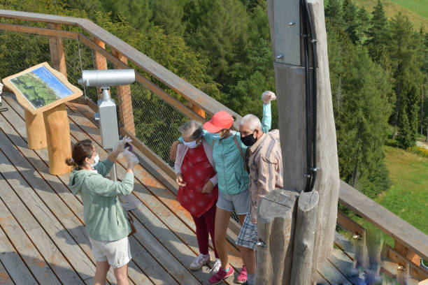 The family in protective masks on a trip on the tower at a height admires the surrounding nature stock photo