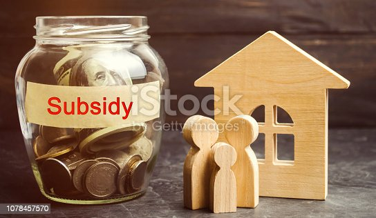 istock The family is standing near a glass jar with the inscription Subsidy. Financial aid, support to the population. Cash grants, interest-free loans. Tax breaks, insurance, low-interest loans 1078457570