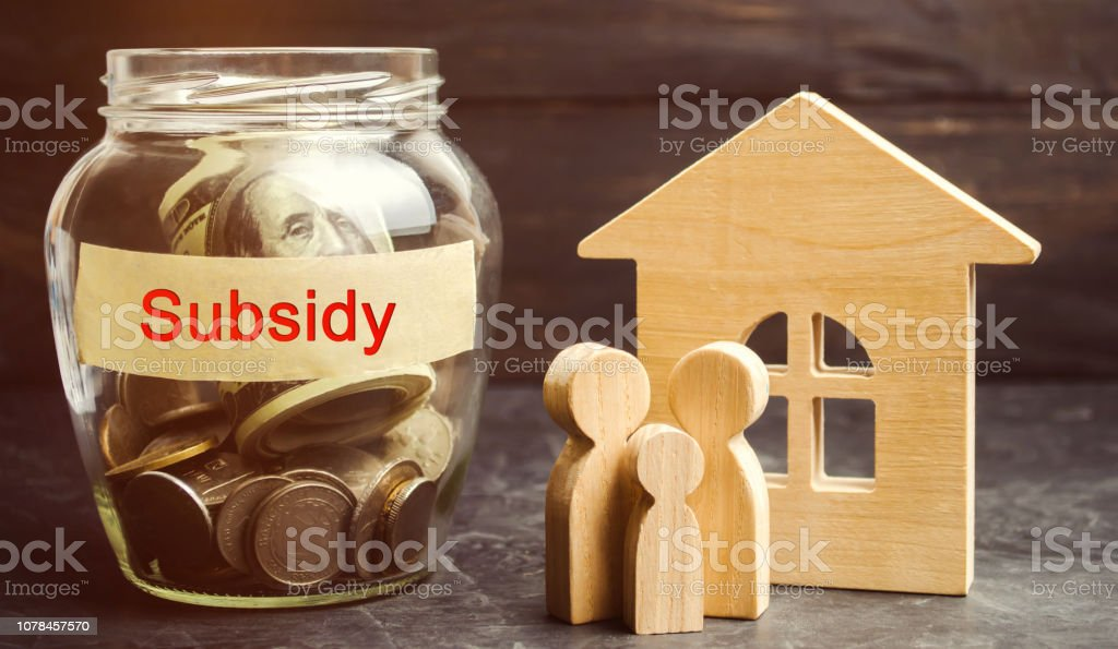 The family is standing near a glass jar with the inscription Subsidy. Financial aid, support to the population. Cash grants, interest-free loans. Tax breaks, insurance, low-interest loans stock photo