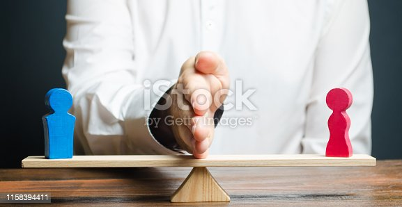 istock The family lawyer shares the figure of a man and a woman on scales. The concept of divorce and division of property. Solving family disputes. Arbitration Services. Gender pay gap 1158394411