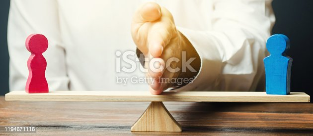 istock The family lawyer shares the figure of a man and a woman on scales. The concept of divorce and division of property. Solving family disputes. Arbitration Services. Gender pay gap 1194671116