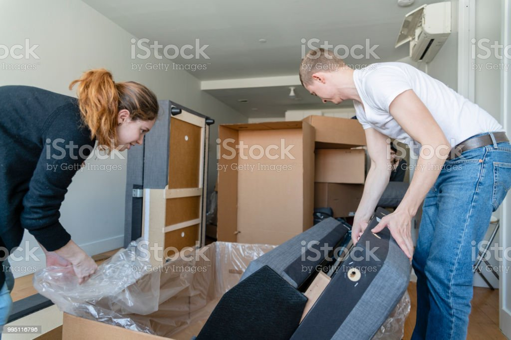 The family moving into the new apartment. The young 30 years old man and teenager girl unboxing and assembling the couch. – zdjęcie