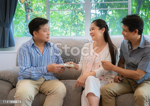 1018458132istockphoto The family of friends gave money to help his friends in economic hardship.Concept of kindness, sincerity towards each other 1141996674