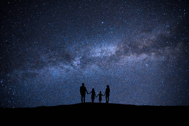 The family standing on the picturesque starry sky background The family standing on the picturesque starry sky background astronomy stock pictures, royalty-free photos & images