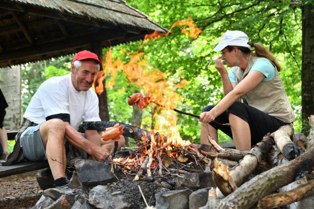 The family toasting sausage together in the woods at the campsite stock photo