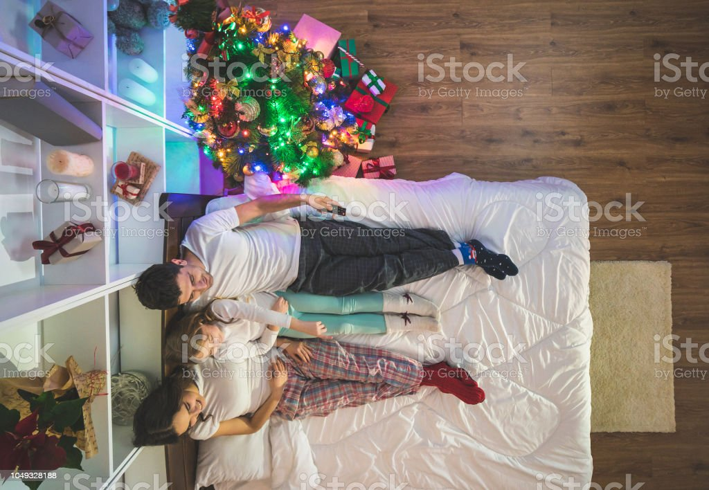 The Family Watch Television On A Bed Near A Christmas Tree View From