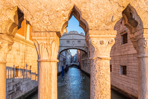 The famous Bridge of Sighs, which connects The Doge's Palace to the New Prisons building, framed in the arches of the Ponte della Paglia in Venice