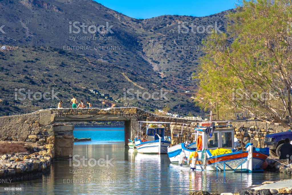 The famous canal of Elounda with the ruins of the old bridge, fishing boats and a group of young winter swimmers, Crete, Greece. stock photo