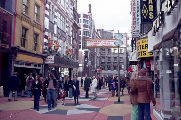 The famous Carnaby Street in London, 70s London, England, UK, 1974. The famous Carnaby Street in London. First pedestrian zone in Europe. Furthermore: shops, boutiques, tourists advertising signs and pedestrians. carnaby street stock pictures, royalty-free photos & images