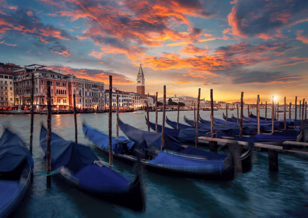 The famous Gondolas are parking on the Canal Grande at sunset in Venice, Italy stock photo