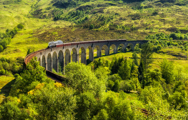 """The famous """"Harry Potte Bridge"""" (Glenfinnan Viaduct) - Scotland 2018 Glenfinnan viaduct (a location made famous in the Harry Potter films) which overlooks Loch Shiel and the Jacobite monument. railway bridge stock pictures, royalty-free photos & images"""