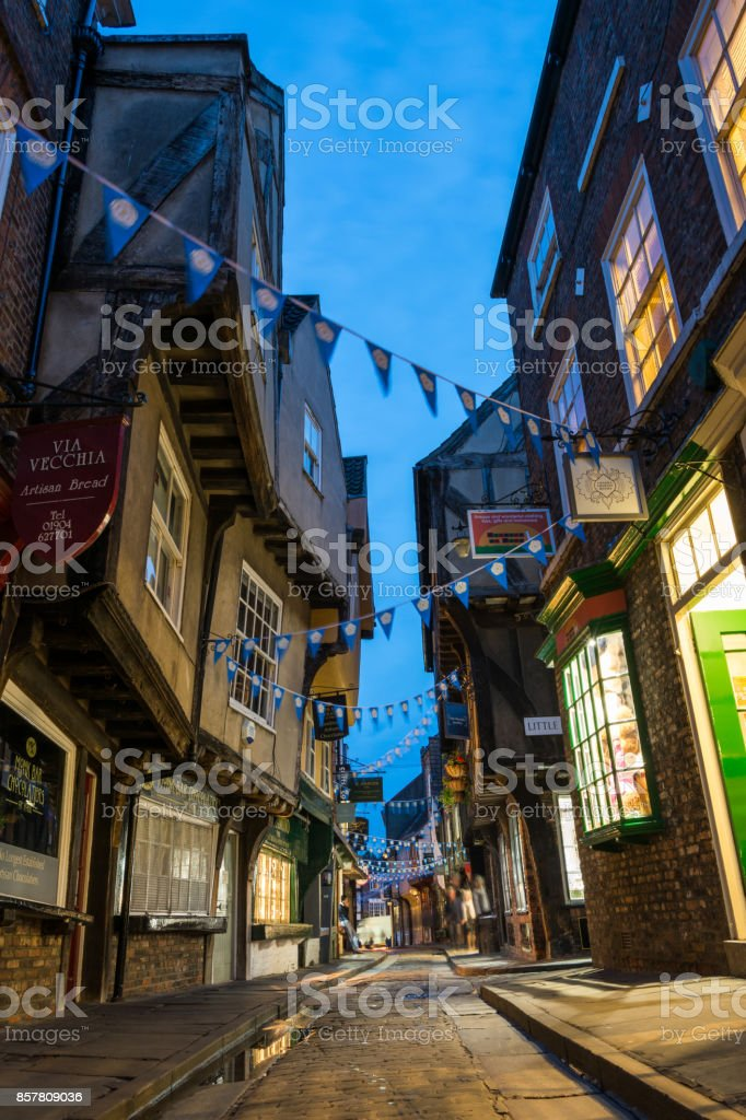 The famous street Shambles with lit shops in York during blue hour stock photo