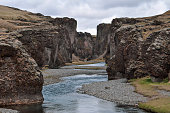 A trickling stream cuts through the mighty, snaking Fjadrargljufur Canyon on a moody summer day - South East Iceland