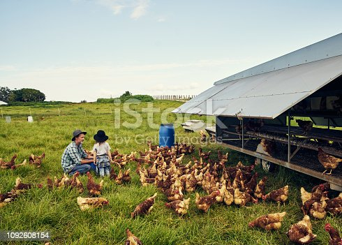 Shot of a father and his little son working on their chicken farm