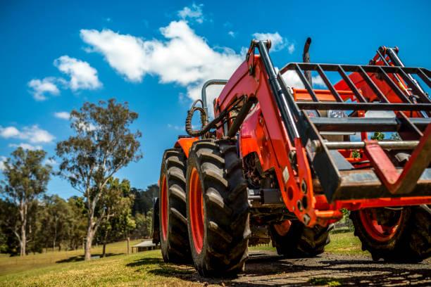 der bauer pflegt seine farm mit einem traktor - waldhandwerk stock-fotos und bilder