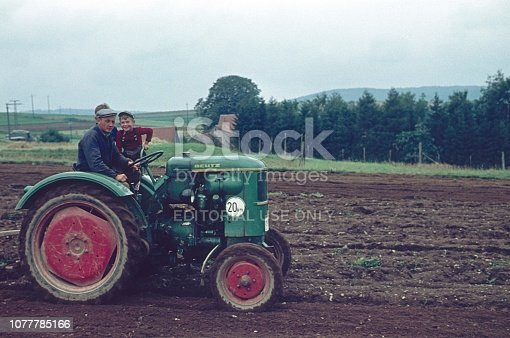 Schönsee, Schwandorf, Bavaria, Germany, 1961. A farmer orders a field with his tractor. His two sons ride with him.
