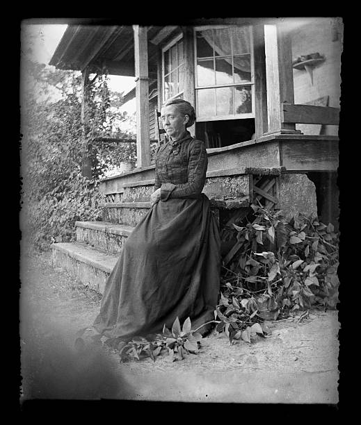 The Farmer's Wife, Circa 1890 Beautiful Black and White portrait of an American Farmer woman wearing Victorian-era clothing. Taken on the front porch of her farmhouse dressed in her best clothes--probably on a Sunday afternoon. The image was digitally restored from a glass plate taken circa 1890. 1890 stock pictures, royalty-free photos & images