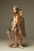 The fashion portrait of young beautiful teen girls in gold dress at studio. The beauty, fashion, glowing, make-up and shinning concepts. Caucasian models