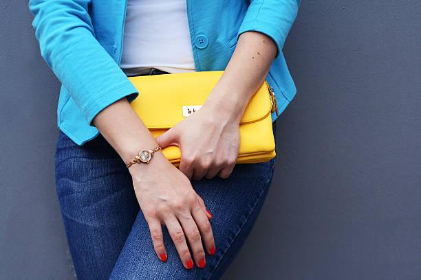 der modische junge frau hält gelb-clutch - handtasche jeans stock-fotos und bilder