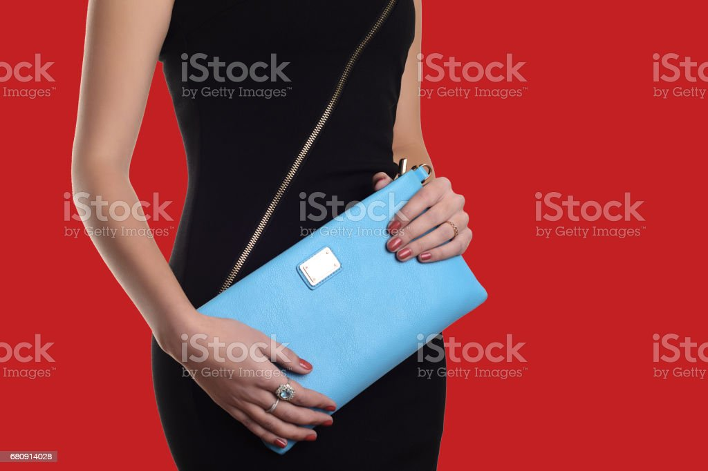 The fashionable young woman in black dress holding blue clutch. Red background royalty-free stock photo