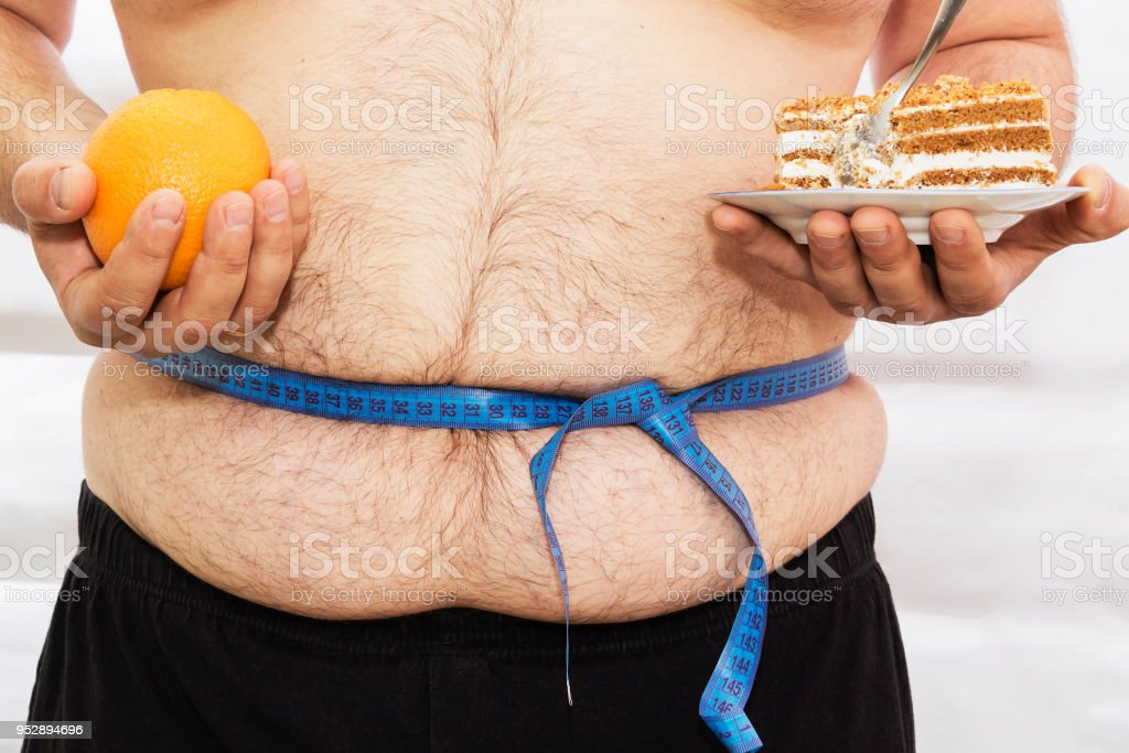 The fat man is tied with a measuring tape. Holds in the hands of cake and oranges. stock photo