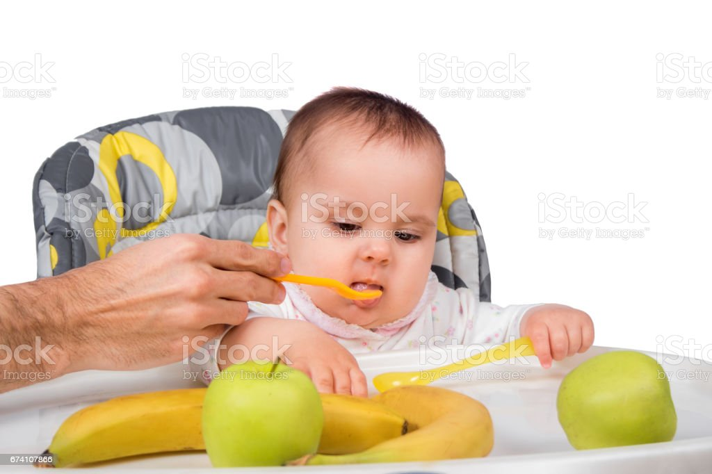 The father feeds with porridge of the one-year-old kid, isolated on the white royalty-free stock photo