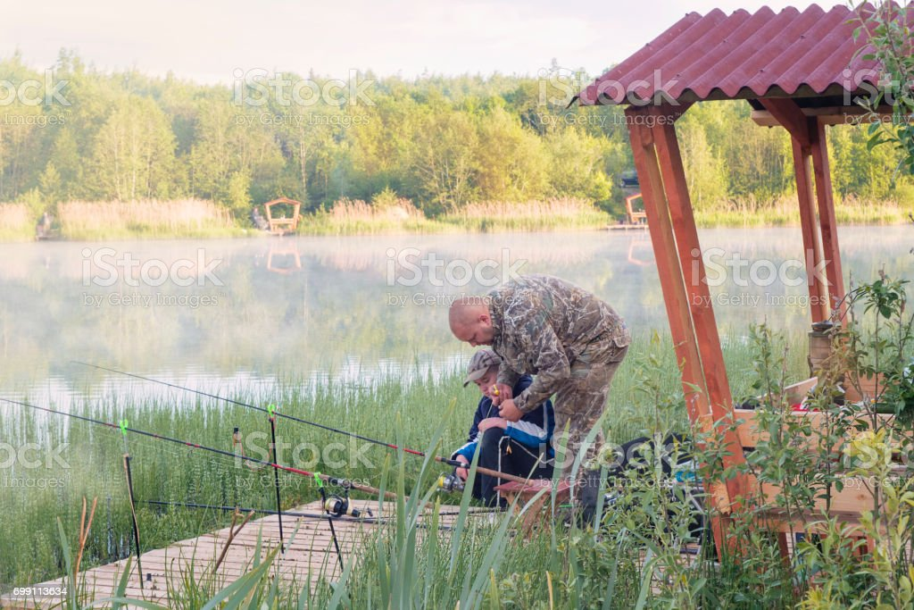 The father trains the son to catch fish on the river bank. stock photo
