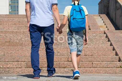 1045032684 istock photo the father walks with his son up the stairs to the school 1061403492