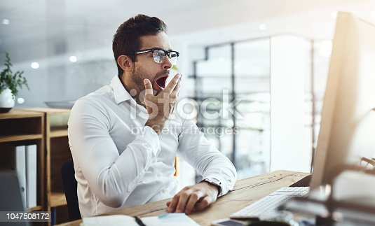 Shot of a young businessman yawning while working in an office