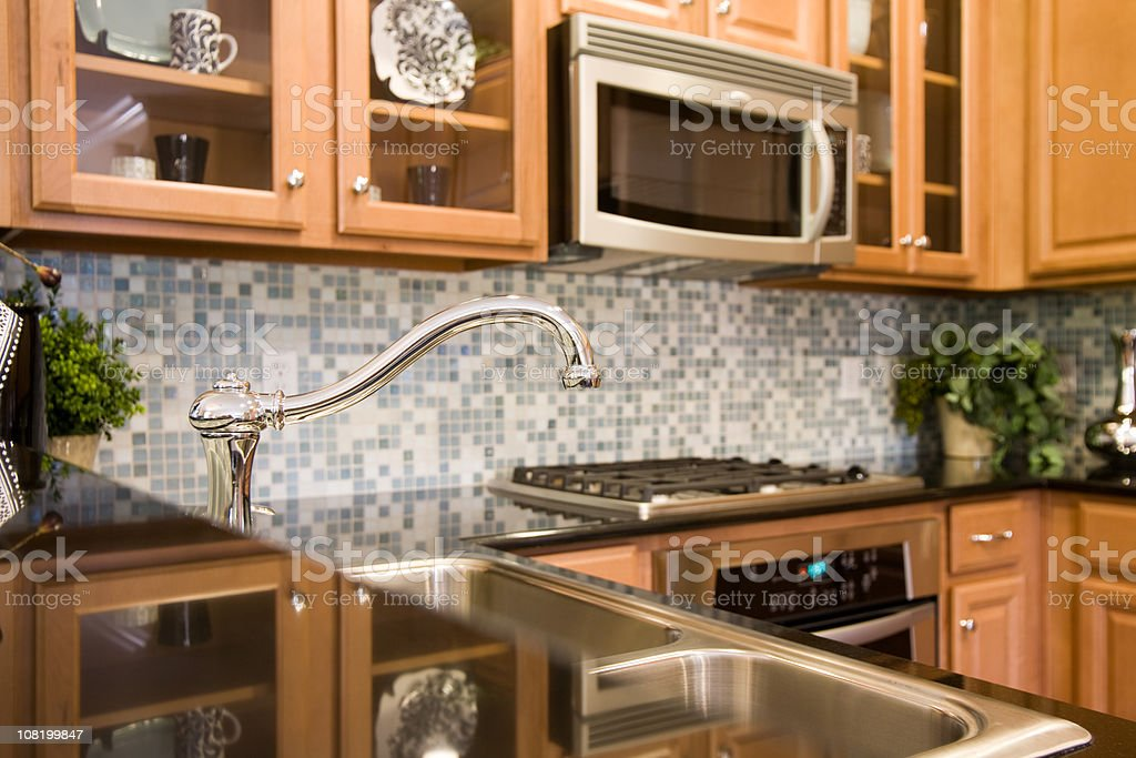The faucet of a modern kitchen with tile backsplash. stock photo