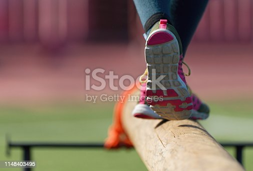 The feet of a athlete as she's walking on a wooden beam outside in the park