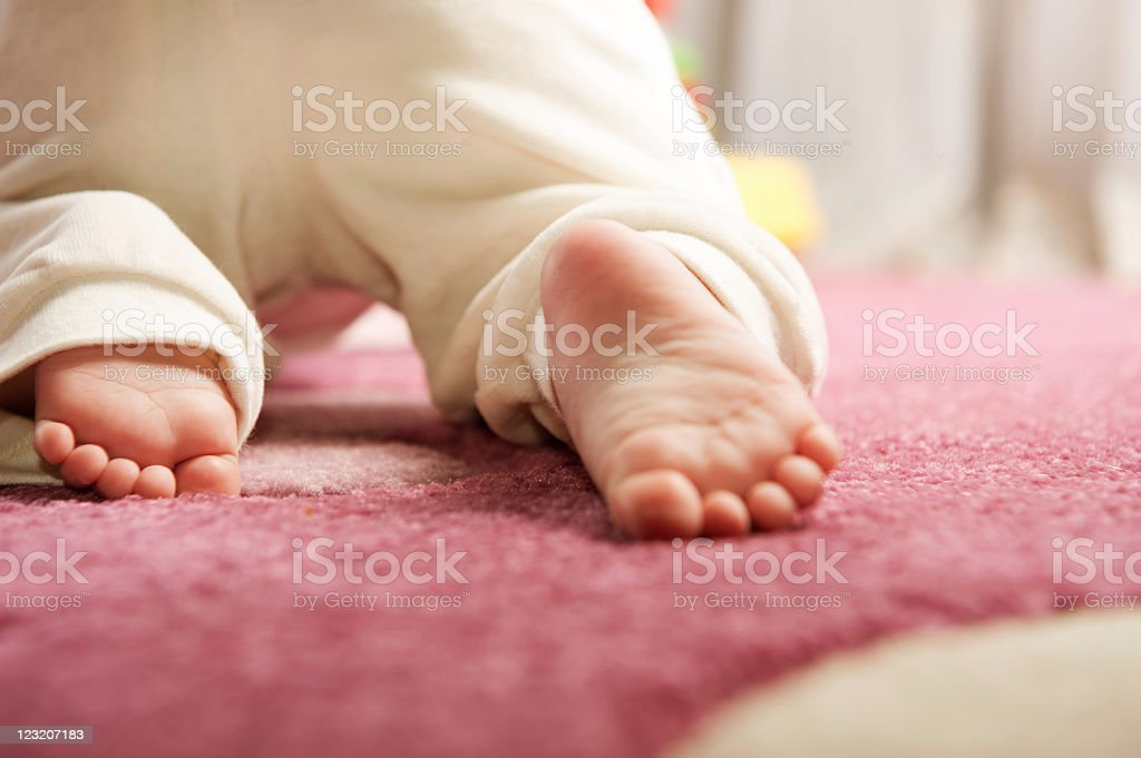 The feet of a baby crawling on a pink carpet stock photo