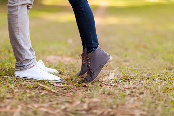 The feet of a teenage couple kissing outside teenage couple kissing outdoors at the park cute teen couple stock pictures, royalty-free photos & images