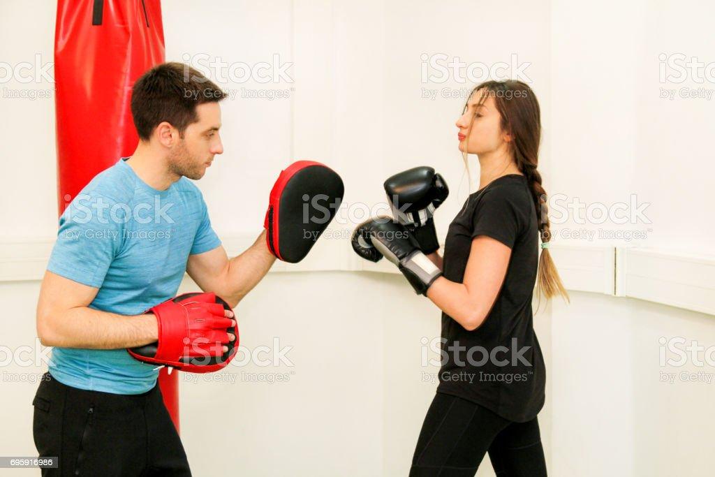 O boxer feminino treino no ginásio. Jovem mulher desportiva perfurando seu parceiro masculino com luvas de boxe vermelhos no clube de ginástica. Garota atraente esportes é praticar com um instrutor bonito no centro esportivo. - foto de acervo