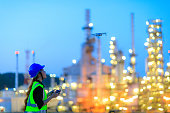 The female engineer using drone for top view inspection the refinery plant.