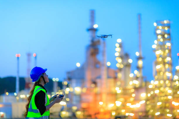 The female engineer using drone for top view inspection the refinery plant. The female engineer using drone for top view inspection the refinery plant. drone point of view stock pictures, royalty-free photos & images
