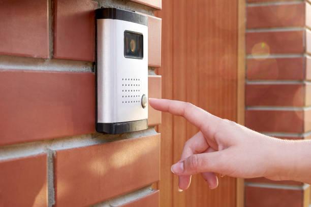 女性の手を押すとカメラとインターホン ボタン ドアベル - 玄関 ストックフォトと画像