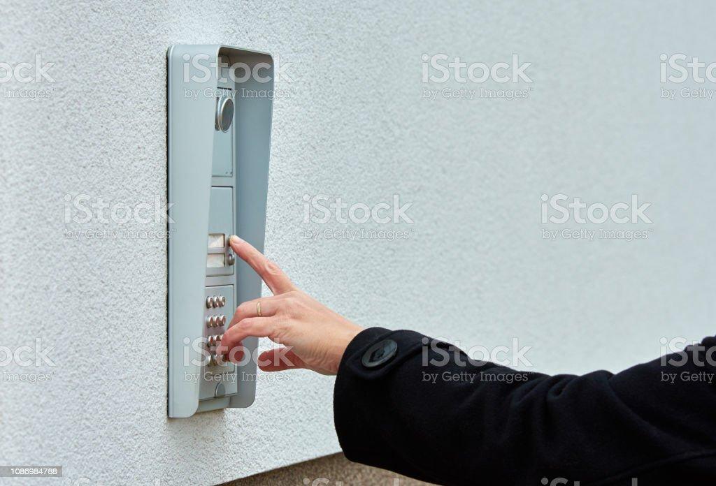 Die Weibliche Hand Drückt Eine Tasteklingel Mit Kamera Und ...
