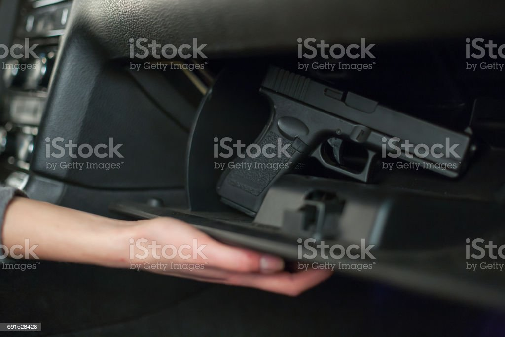The female hand pulls out a gun from the glove box in the car. stock photo